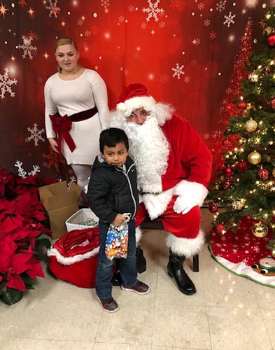 child with Santa at holiday party